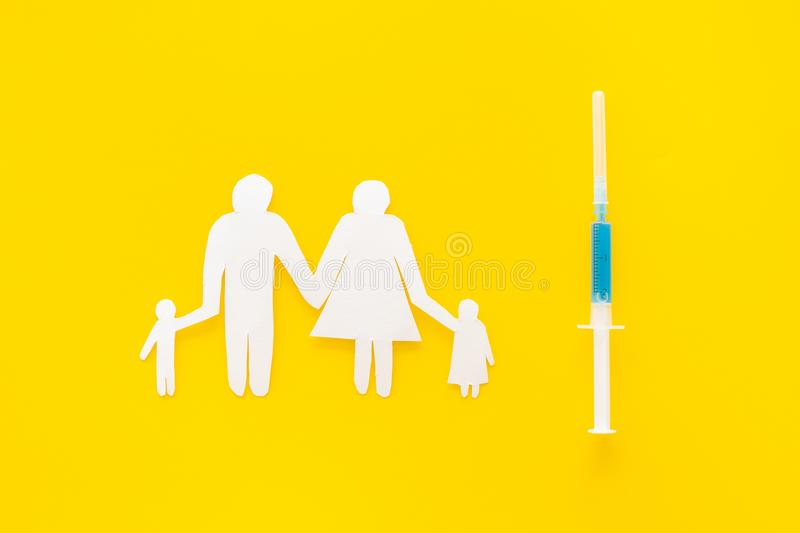 Vaccination for healthy family, vacctination of children. Flu. Syringe near family cutout on yellow background top view.  royalty free stock photo