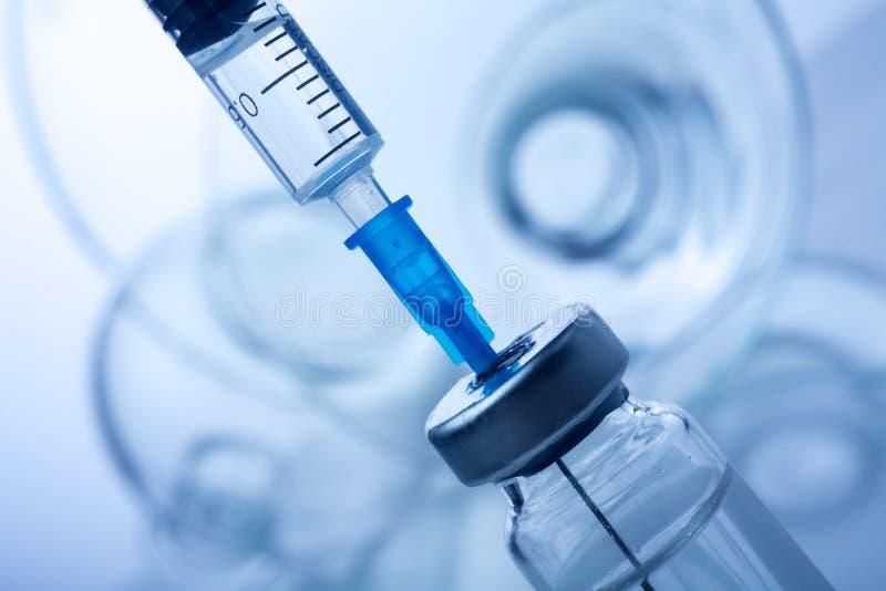 Vaccine vial dose flu shot drug needle syringe,medical concept vaccination hypodermic injection. On blue background stock images