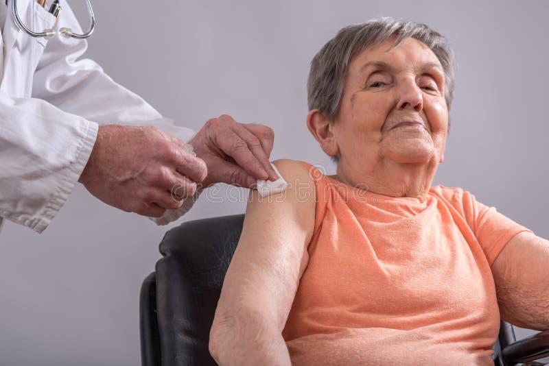 Vaccinering av en äldre kvinna arkivbild