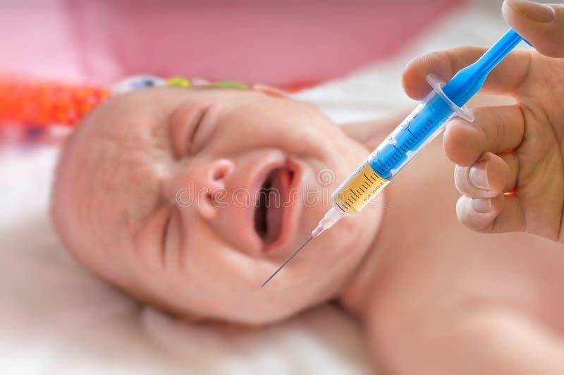 Vaccineringbegrepp - injektionssprutan och gråt behandla som ett barn royaltyfri bild