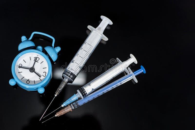 Vaccineringtid Vaccin i liten medicinflaska med injektionssprutan på klockabakgrund Förhindrandeimmuniseringsjukdom royaltyfri foto
