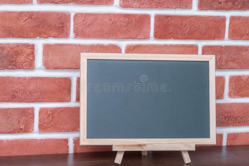 Vacie al tablero en blanco del negro de la tiza en fondo del ladrillo rojo fotos de archivo libres de regalías