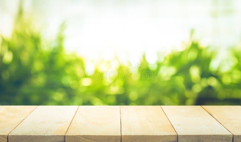Vacie de la sobremesa de madera con el fondo del jardín del verde de la falta de definición imagenes de archivo