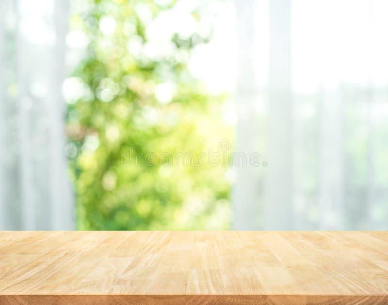 Vacie de la sobremesa de madera en la falta de definición de la cortina con la opinión de la ventana fotografía de archivo libre de regalías