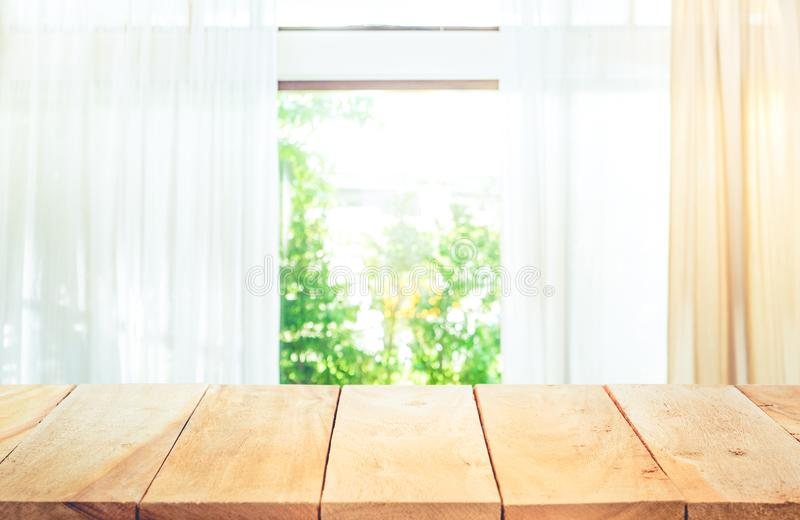 Vacie de la sobremesa de madera en la falta de definición de la opinión de la ventana de la cortina foto de archivo