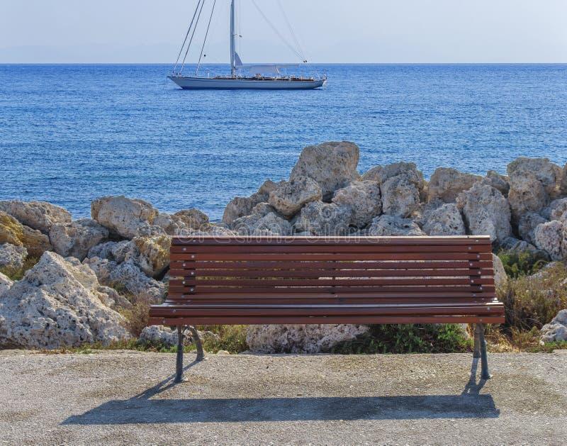 Vacie el banco de madera en el muelle del barco con el mar y el muelle azules hermosos imagenes de archivo