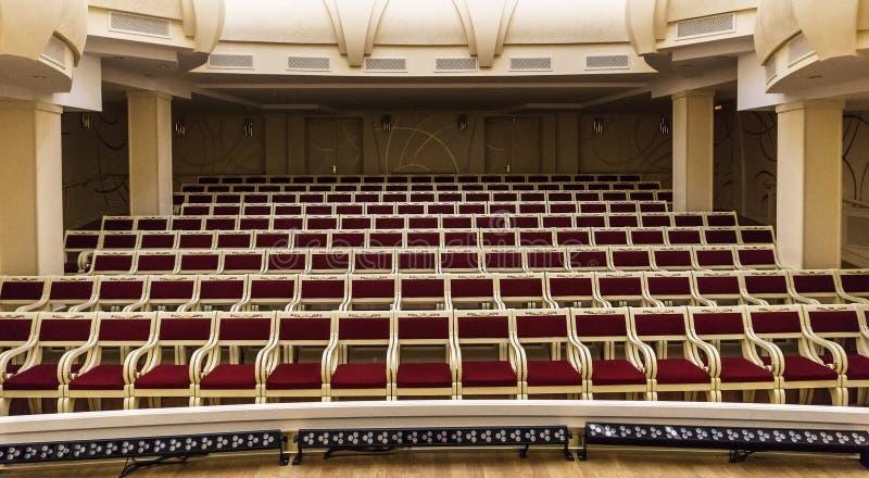 Vacie el interior enorme del pasillo con filas de sillas rojas fotos de archivo libres de regalías