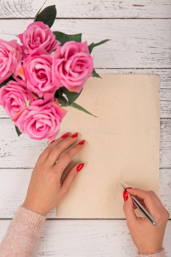 Vacie el papel en blanco con las manos del ` s de la mujer Fondo con las rosas rosadas en florero imágenes de archivo libres de regalías