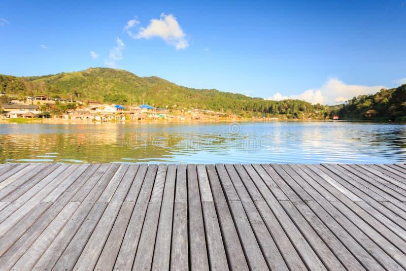 Vacie el piso o el decking de madera al lado del lago imagenes de archivo