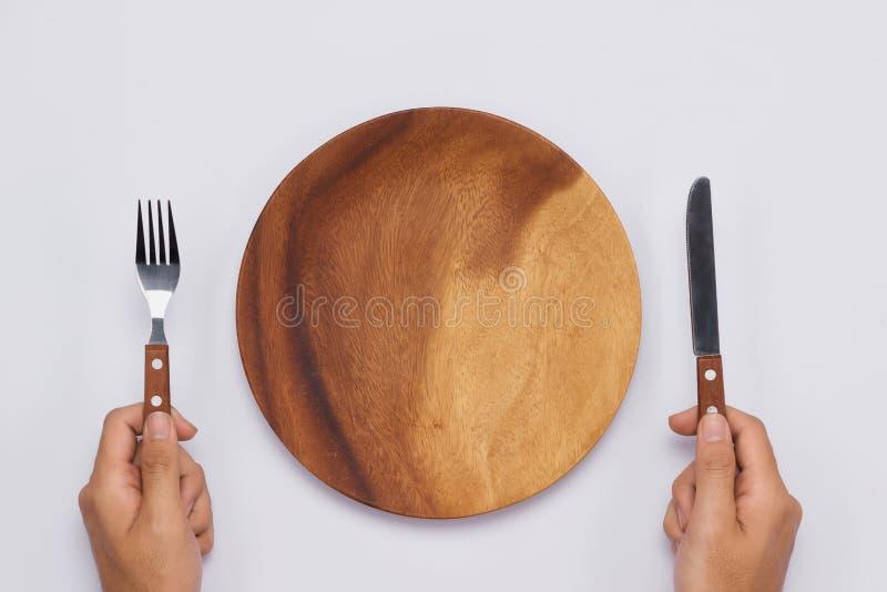 Vacie el plato de madera con el cuchillo y la bifurcación en manos Visión superior imagen de archivo libre de regalías