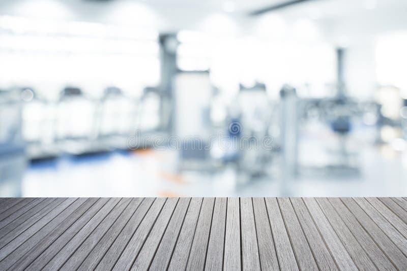 Vacie el top de la tabla de madera y borroso de fondo del gimnasio de la aptitud fotografía de archivo