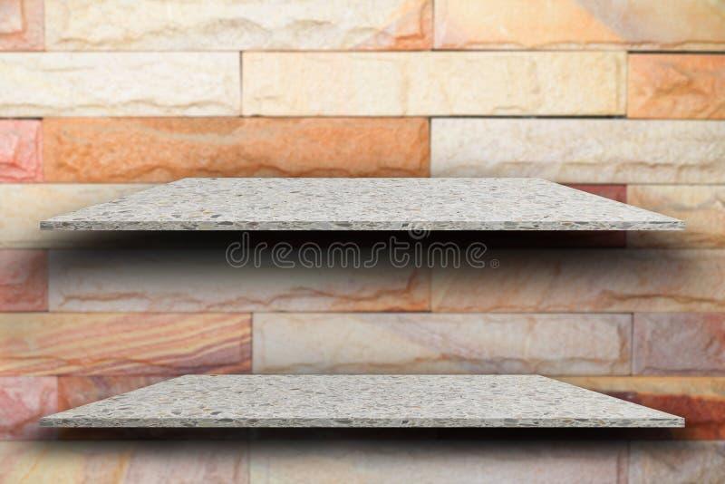 Vacie la piedra pulida estante del top dos y empañe el fondo de la pared de ladrillo imagen de archivo libre de regalías