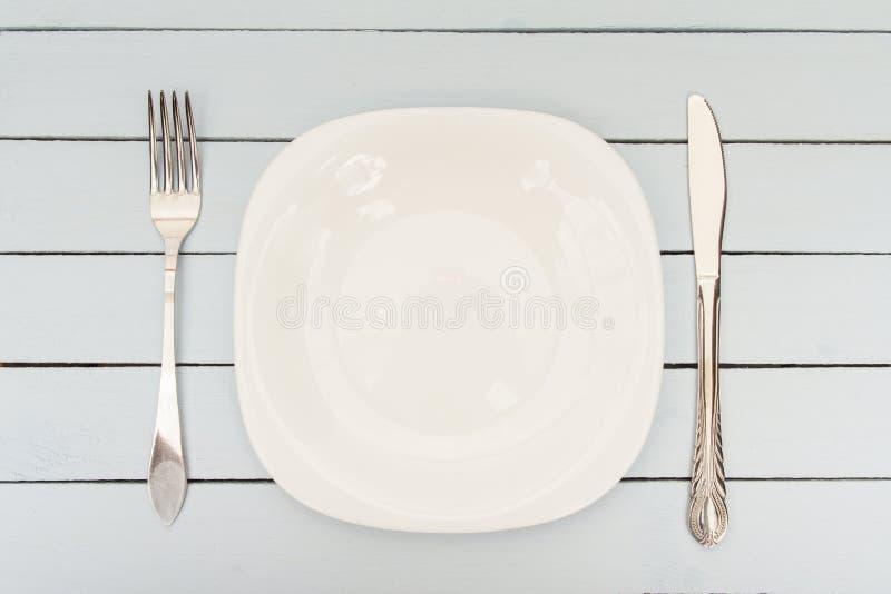 Vacie la placa, la bifurcación y el cuchillo blancos en la tabla de madera Plantilla para el menú o el diseño Visión superior fotografía de archivo