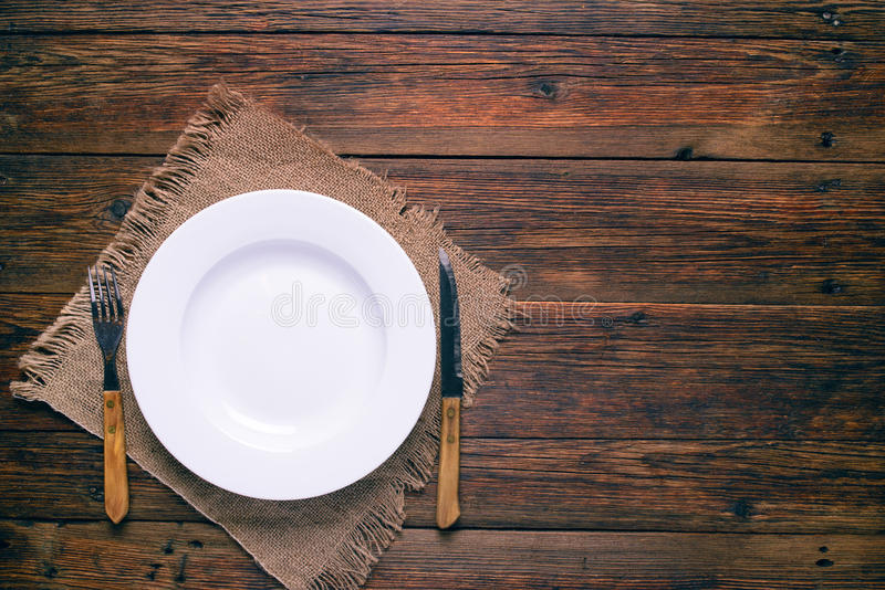 Vacie la placa blanca con la bifurcación y el cuchillo en fondo de madera rústico foto de archivo libre de regalías