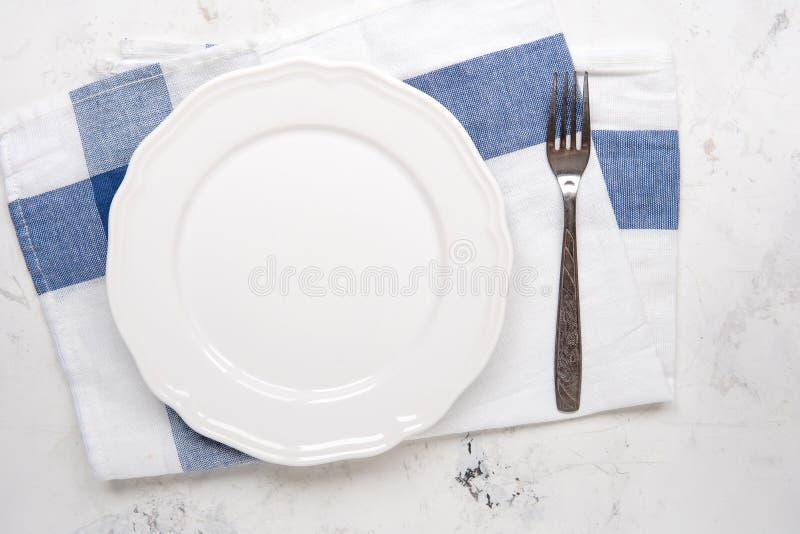 Vacie la placa blanca y bifurque en una tabla, visión superior fotografía de archivo