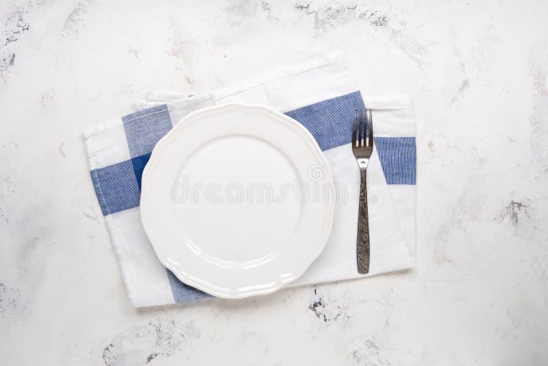 Vacie la placa blanca y bifurque en una tabla, visión superior foto de archivo