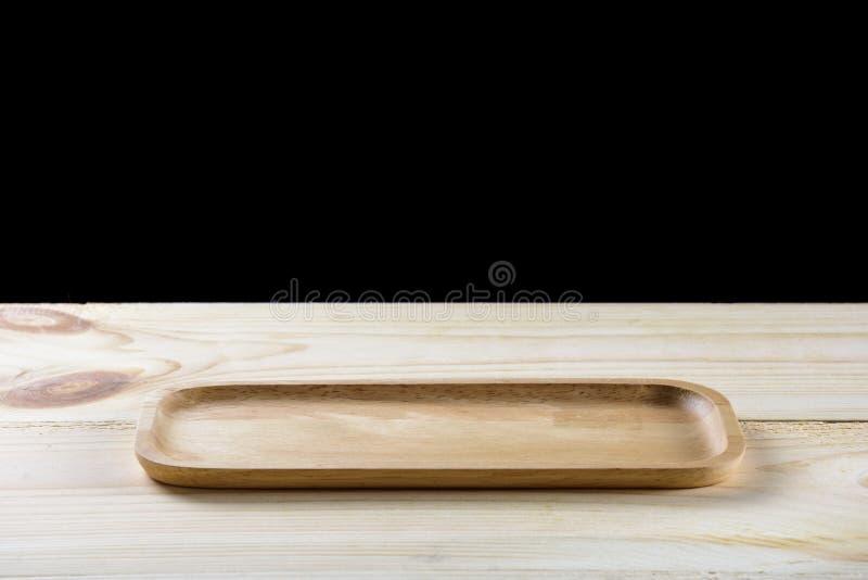 Vacie la placa de madera en la tabla de madera aislada en negro fotografía de archivo