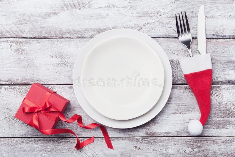 Vacie la placa y la decoración blancas en la opinión de sobremesa rústica de madera Concepto del ajuste de la tabla de la Navidad imagen de archivo libre de regalías