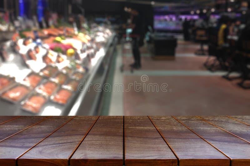Vacie la plataforma de espacio de madera de la tabla y el pasillo borroso del supermercado fotos de archivo libres de regalías