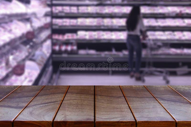 Vacie la plataforma de espacio de madera de la tabla y el pasillo borroso del supermercado foto de archivo libre de regalías