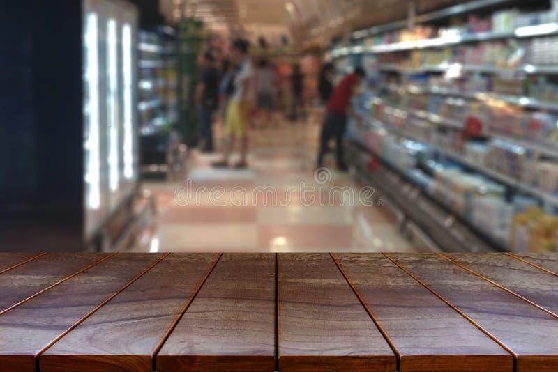 Vacie la plataforma de espacio de madera de la tabla y el pasillo borroso del supermercado fotos de archivo