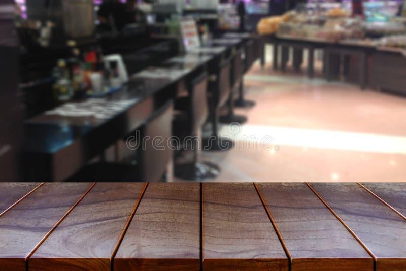 Vacie la plataforma de espacio de madera de la tabla y el pasillo borroso del supermercado imagenes de archivo