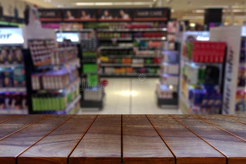 Vacie la plataforma de espacio de madera de la tabla y el pasillo borroso del supermercado imagen de archivo libre de regalías