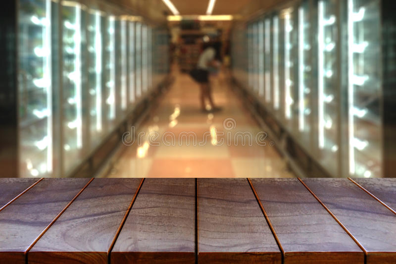 Vacie la plataforma de espacio de madera de la tabla y el pasillo borroso del supermercado imágenes de archivo libres de regalías