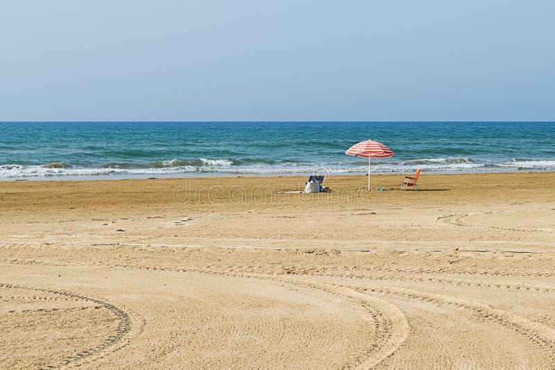 Vacie la playa arenosa con un parasol en la costa costa imagenes de archivo
