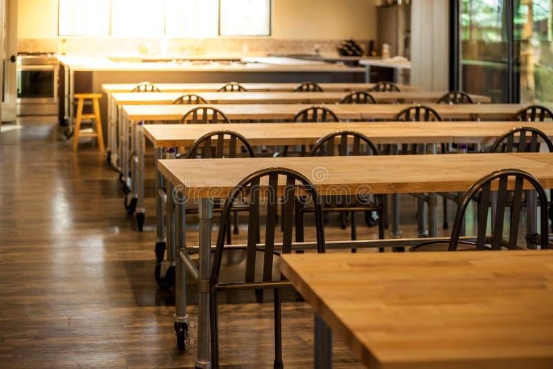 Vacie la sala de clase culinaria de la escuela con filas de tablas y de sillas fotos de archivo