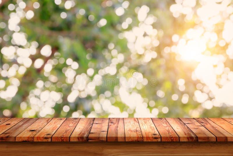 Vacie la tabla de madera con el fondo del verde del extracto del bokeh imagenes de archivo