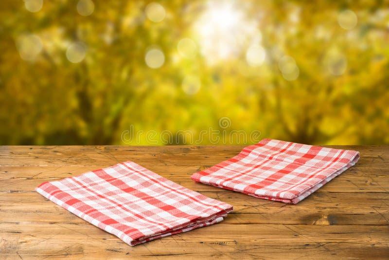 Vacie la tabla de madera con el mantel sobre fondo del parque de naturaleza del oto?o foto de archivo libre de regalías
