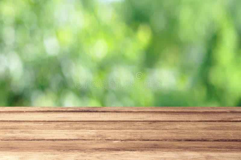 Vacie la tabla de madera con tema al aire libre del bokeh del jardín imagenes de archivo