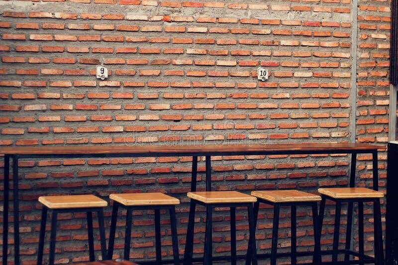 Vacie la tabla y las sillas de madera para la comida de la calle, texto de la pared de ladrillo imagenes de archivo