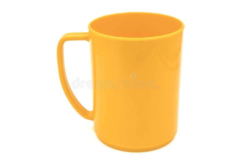Vacie la taza plástica anaranjada aislada en el fondo blanco del fichero con la trayectoria de recortes imagen de archivo libre de regalías