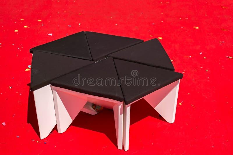 Vacie las sillas negras en la alfombra roja con confeti imagen de archivo
