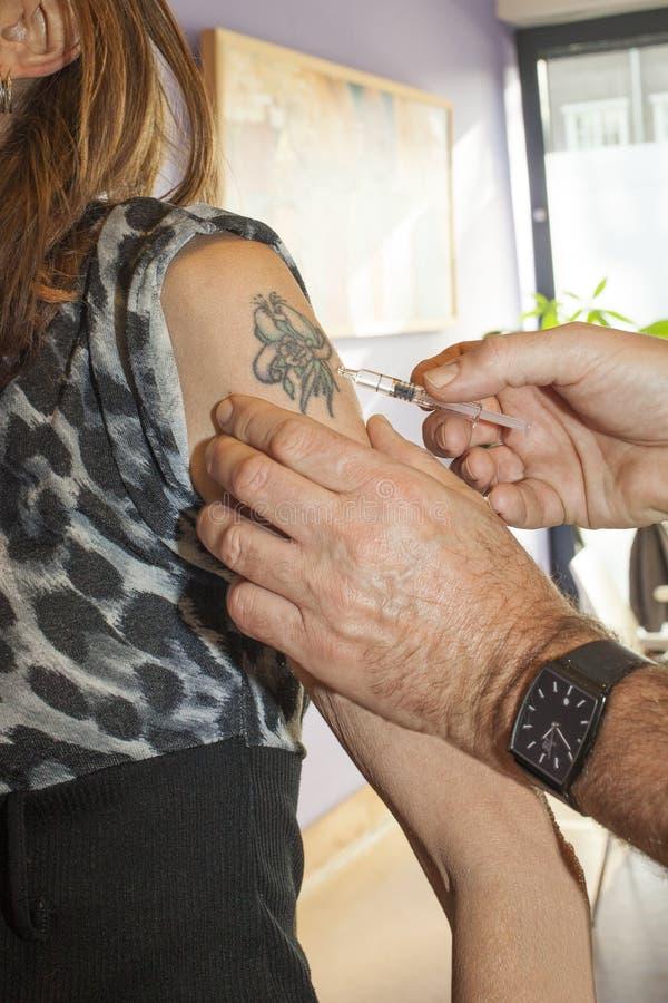 Vacina contra a gripe no braço imagem de stock