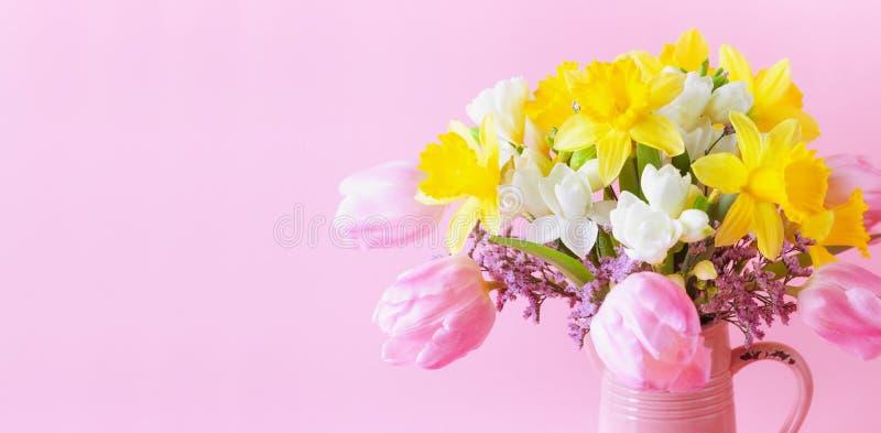 Vacker vårsammansättning med färgade blommor i rosa vase Mödrar eller mödrar med hälsningskort för kvinnor royaltyfri foto