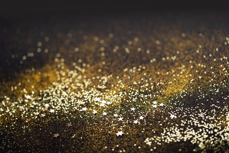 Vackers julljus - bakgrund Konstrukna glitterbågar och spridda glitterkler i guldfärg, på svart fotografering för bildbyråer