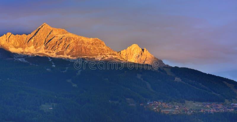 Vackert berg vid solnedgången ovanför alpina byn arkivfoton