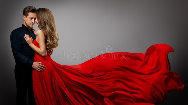 Vackert par, Fashion Woman in Red Silk Dress and Elegant Man Studio Portrait, Fluttering Gown royaltyfri foto