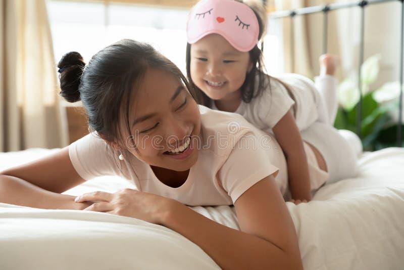 Vackert vietnamesisk kvinna som ligger på sängen med dotter på baksidan royaltyfri bild