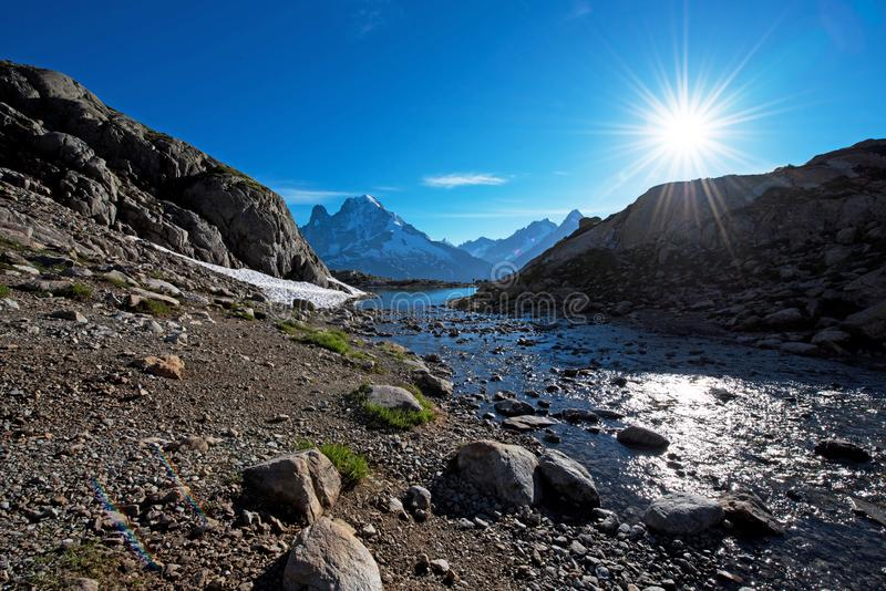 Vackra bergslandskap med stenar och sol ovanför bergsfloden i franska Alperna, massiv La Blanc Harmony, turism, arkivbilder