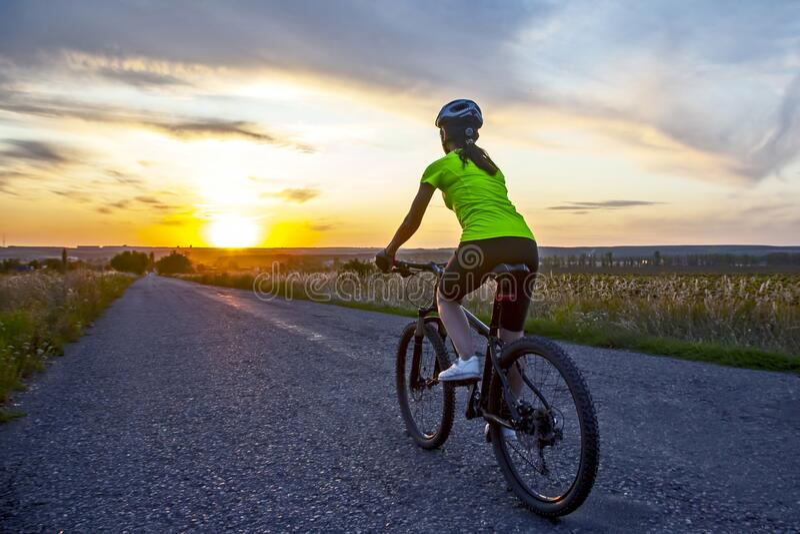 Vackra flickcyklister cyklar på väg i solnedgången arkivbilder