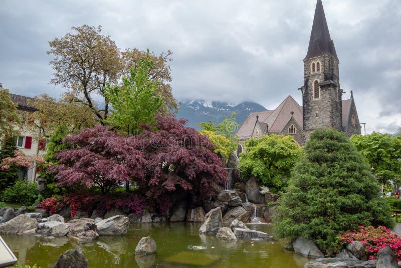 Vackra friska trädgårdar med damm på kyrka och molnhimlens bakgrund i Europa royaltyfria foton