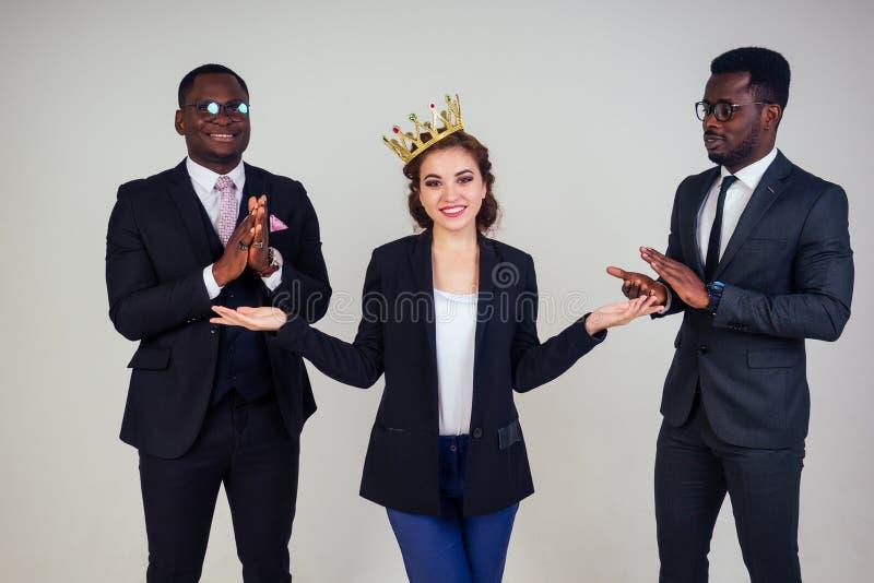 Vackra indianska affärskvinna och två afrikanska affärsmän som applåderar i studion på vit bakgrund royaltyfri foto