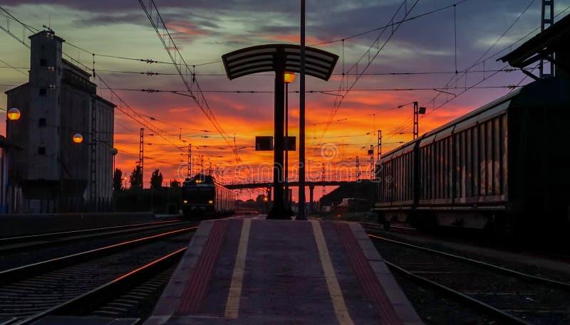 Vackra järnvägsstationer med röd solnedgång som anländer till ett tåg i Spanien arkivbilder