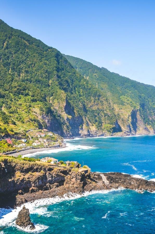 Vackra klippor på Atlantens kust av byn Seixal, Madeira, Portugal Strålgropar, små städer och royaltyfria bilder