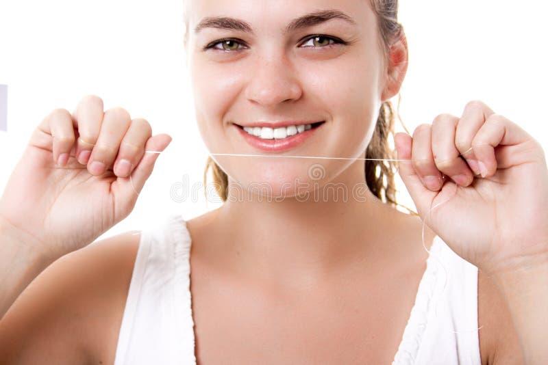 Vackra kvinnor som leker med friska tänder som håller tandtråd i händerna arkivbild