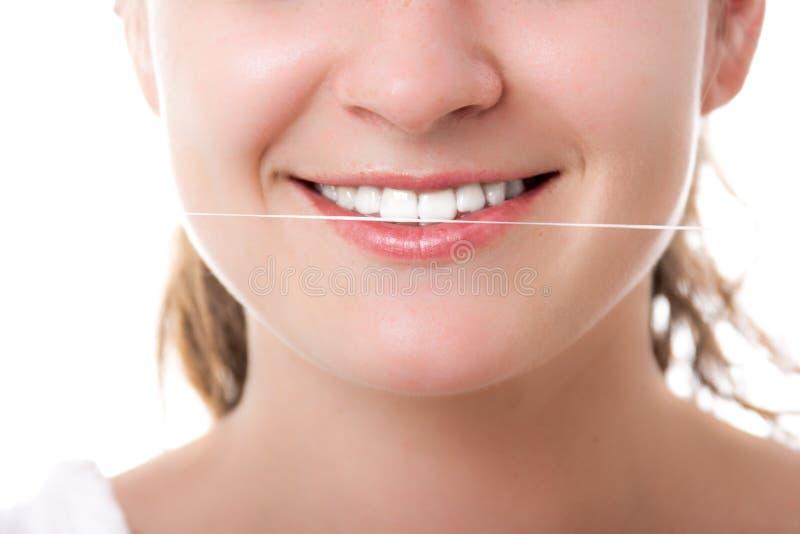 Vackra kvinnor som leker med friska tänder som håller tandtråd arkivfoto